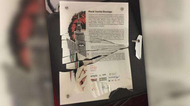 Zniszczona tablica przed muralem Bowiego Miasto Jest Nasze - Żoliborz